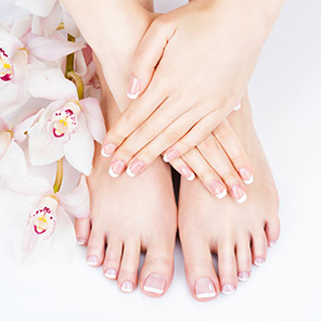 woman's manicured hands and pedicured feet with a bouquet of orchids