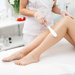 woman getting her legs professionally waxed